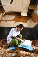 Staff Nurse Charu Thapa Magar looks into a log book in the destroyed district hospital building in Trishuli, Nuwakot