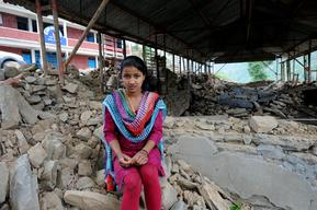 Laxmi Giri, 15, a grade 10 student sits in front of her destroyed school in Balefi
