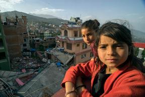Twin sisters Jamuna, right, and Ganga Nepali, 9, survey the surrounding damage from atop the apartment where they used to live in the town of Charikot
