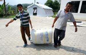 Staff of Spinal Injury Rehabilitation Center carry a sack of blankets provided by UNICEF