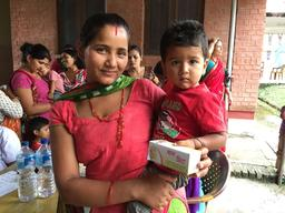 A mother and her young child receive micro nutrient powder Bal Vita at UNICEF-supported out-patient therapeutic programme (OTP) clinic in Kamalamai