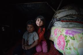 Jamuna Nepali, 9, hugs her 4 year old brother Anuj in the tent in which they are staying