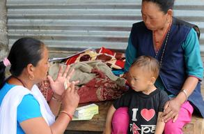 Female community health volunteer (FCHV) Manju Lama explains Phulmaya Lama, mother of two-year-old Raj, how to use Bal Vita (multiple micronutrient powder)