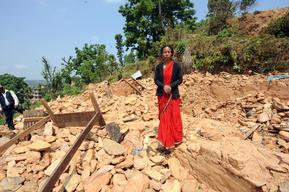 Saraswoti Karki stands amid the rubbles of her destroyed house
