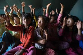 Jamuna Nepali, 9, her sister Ganga, right, and other children attend a UNICEF-supported Child Friendly Space