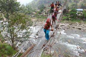 Young girls and women cross a river on a damaged suspension bridge in Dhodeni