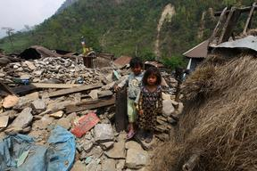 A young boy and girl stand amid the rubbles of a destroyed house in Baluwa