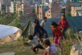 Jamuna Nepali, 9, center, plays with other children in the tent camp for earthquake-displaced people