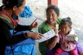 Female community health volunteer (FCHV) Krishnaa Tamang explains Anjana Tamang, mother of three-year-old Bipasa,  how to use Bal Vita (multiple micronutrient powder) at Mulkharka village